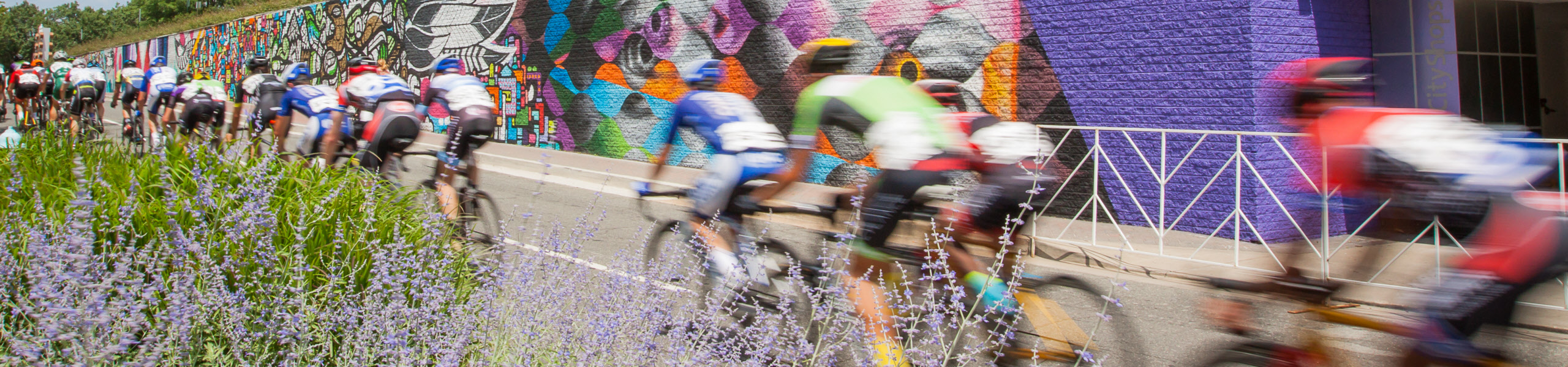 bike racing pack passes purple mural wall